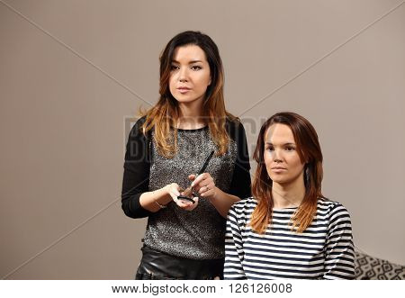 Preparing for an important meeting - Makeup. Beautiful girl visagist does make-up to the client of a beauty salon. Girls looking at the reflection in the mirror.