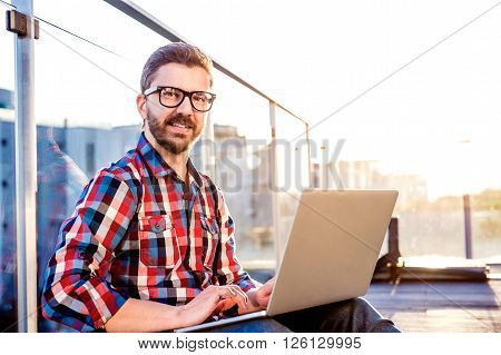Young businessman writing on a laptop computer, sitting on the balcony