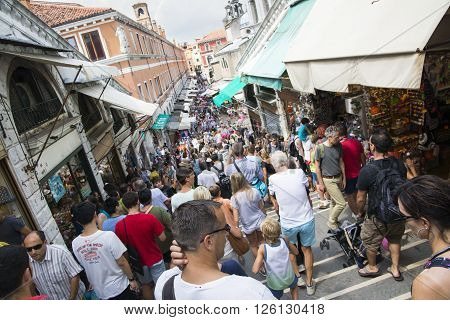 VENICE,ITALY-AUGUST 12,2014:many people go walking watching the scenery and the shops on the Rialto Bridge in Venice during a sunny day.