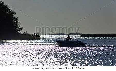 RAUMA, FINLAND ON JULY 03. View from the shore of an unidentified man cruising the inlet on July 03, 2013 in Rauma, Finland. Slow speed ahead in the summer night. Editorial use.