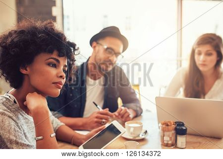 Close up portrait of young african woman with digital tablet and people in background at a cafe table. Young people sitting at a restaurant with laptop and digital tablet.