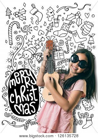 Cute Little Asian Girl Is Playing Guitar About Christmas
