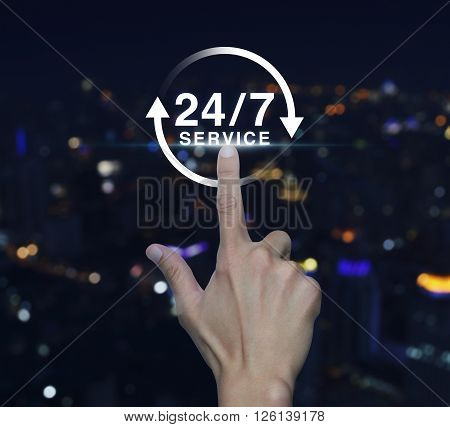 Hand pressing button 24 hours service icon over blurred light city tower background Full time service concept