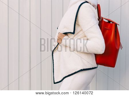 Fashionable beautiful big red backpack on the arm of the girl in a fashionable white sports suit, posing near the white wall on a warm summer night. Part of the body.  Warm color