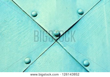 Metallic steel turquoise surface of old metal plates with rivets above. Industrial rough metal background.