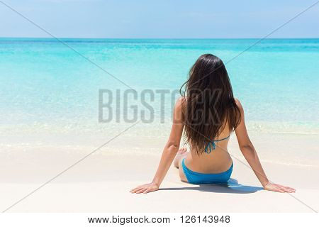 Beach relaxation bikini suntan woman lying down relaxing sunbathing sun tanning on perfect white sand and pristine turquoise water. Idyllic tropical getaway luxury island life.