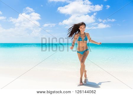 Happy beach summer fun Asian bikini woman running of joy on amazing white sand enjoying holidays on Caribbean tropical travel to paradise destination. Cheerful young girl on exotic getaway vacation.