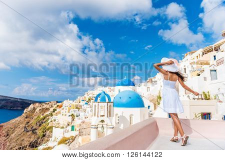 Europe tourist travel woman in Oia, Santorini, Greece. Happy young woman looking at famous blue dome church landmark destination. Beautiful girl in white dress on visiting the Greek island.