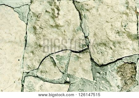 Stone background in vintage tones - surface of broken rough stone with deep cracks