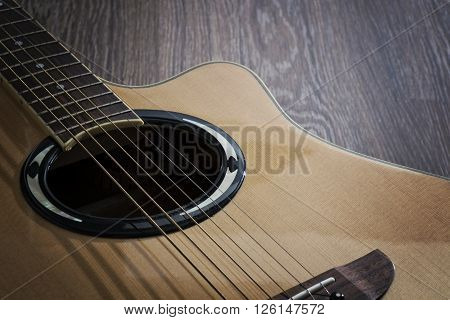 An acoustic guitar laying on the wooden floor ** Note: Soft Focus at 100%, best at smaller sizes