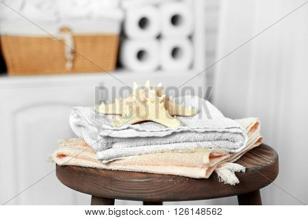 Bathroom set with towels and starfish on stool in light interior