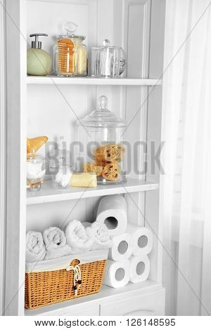 Bathroom set with towels, sponges and dispensers on a shelf in light interior