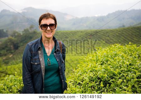 Smiling woman is on the tea plantations in the mountainous district of Cameron Highlands, Malaysia.