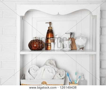 Bathroom set with towels, toothbrushes and sponge on a shelf in light interior