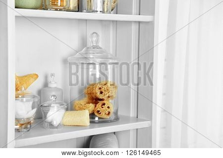 Bathroom set with sponges and dispenser on a shelf in light interior