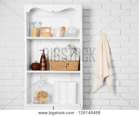 Bathroom set with towels, toothbrushes and basket on a shelf in light interior