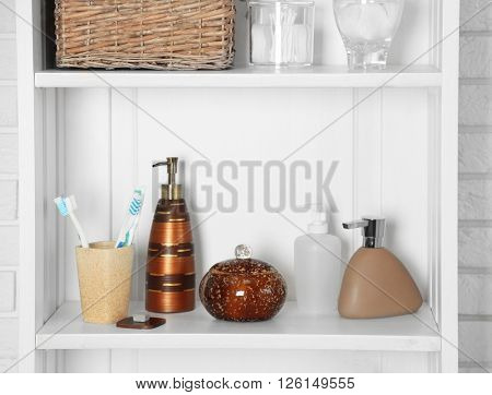 Bathroom set in a shelf with toothbrushes and dispensers on a shelf in light interior