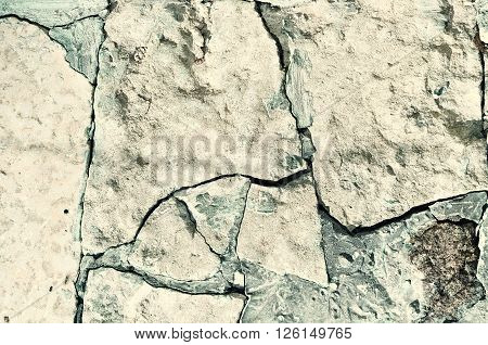 Old broken pale stone with deep light green cracks. Concrete textured rough background