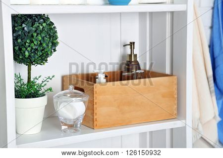 Bathroom set with box, sponges and dispensers on a shelf in light interior
