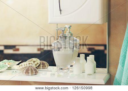 Liquid soap with green salt and shells on a shelf in bathroom
