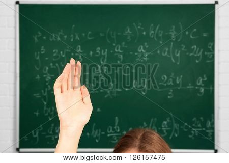 Raised hand on blackboard background in class