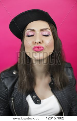 Beautiful young woman with closed eyes sends a kiss. Lips in focus. Black snapback cap and leather jacket. Pink background