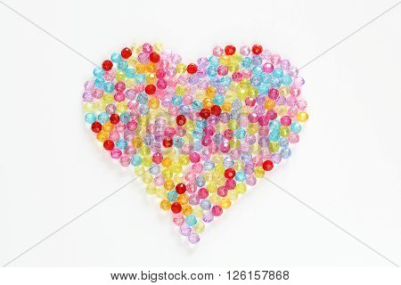 Colorful beads in the shape of a heart for background and backdrop