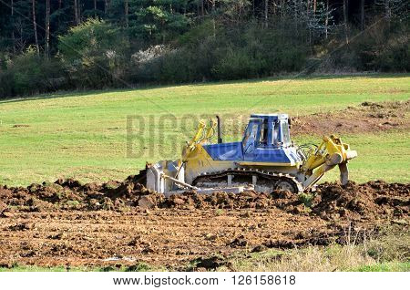 Yellow blue bulldozer working on green field