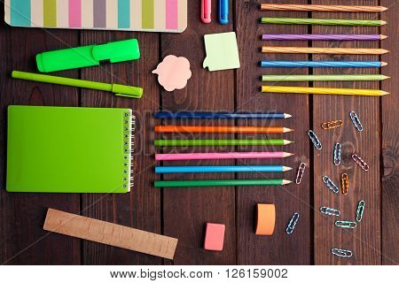 School set with notebooks, colored pencils and clips on wooden background