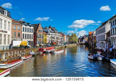 Ghent, Belgium - April 12, 2016: View of old colorful traditional houses along the canal and boats in popular touristic destination Ghent, Belgium
