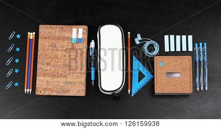 School supplies near blackboard, close up