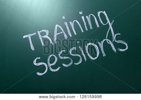 Training sessions inscription written with white chalk on blackboard