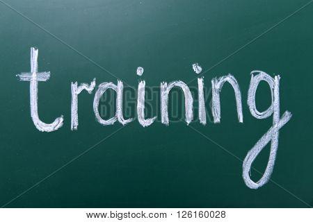 Training inscription written with white chalk on blackboard