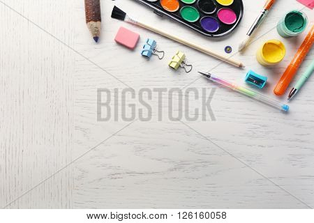 Office supplies on light wooden background