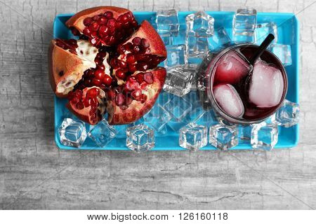 Fresh cocktail with pomegranate on grey table background, top view