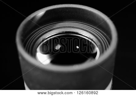Lens of eyepiece with rubber eyecup. Selective focus. Macro. Close up view. Vintage photo. Black and white.