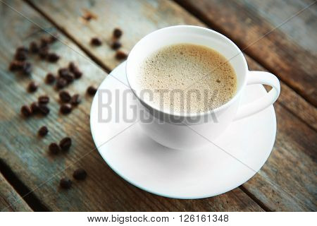 Cup of fresh coffee with beans on wooden background