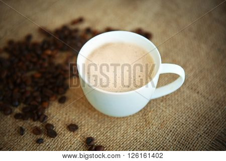 Cup of coffee with beans on sackcloth background
