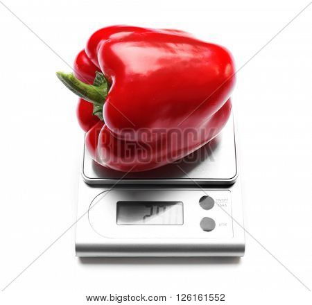 Red bell pepper on digital kitchen scales, isolated on white
