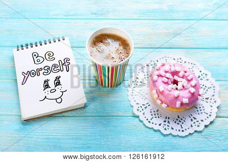 Cup of coffee with doughnut and note BE YOURSELF on wooden background