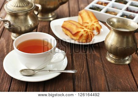 Cup of tea and pastry filled with custard on wooden background