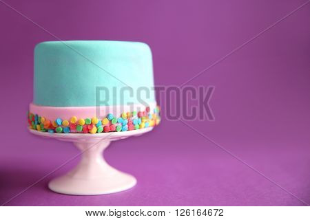 Birthday cake with sprinkles on purple background.