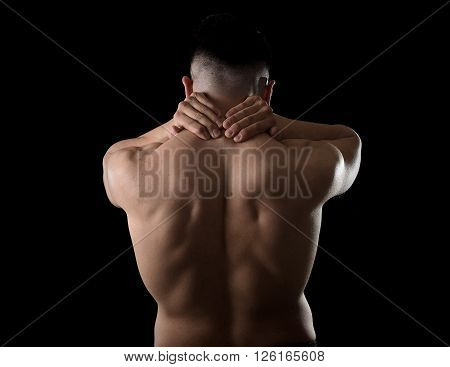 back of young muscular sport man holding sore neck with his hands and touching or massaging cervical area suffering body pain in spine back health problem isolated on black background