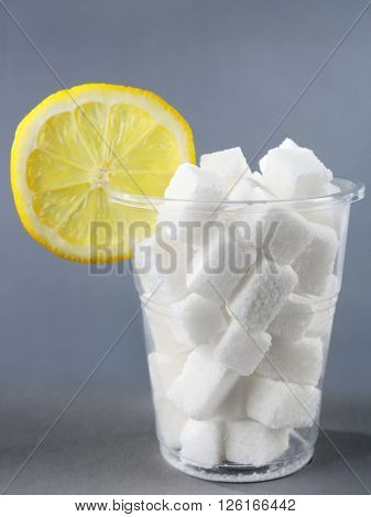 Plastic glass full of sugar with lemon on grey background