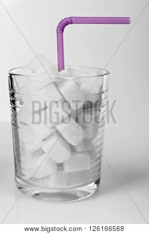 Old fashioned glass with lump sugar and cocktail straw on grey background