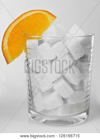 Old fashioned glass with lump sugar and slice of orange on grey background