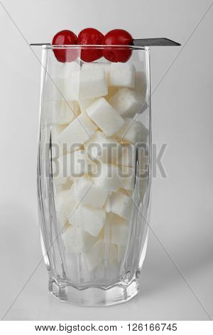 Highball glass with lump sugar and cocktail cherries on grey background