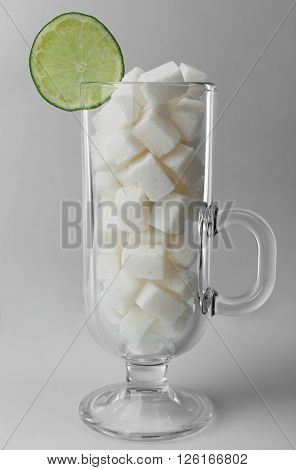 Irish coffee glass with lump sugar and slice of lime on grey background