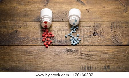 Scattered from medical bottle red and blue pills on wooden background
