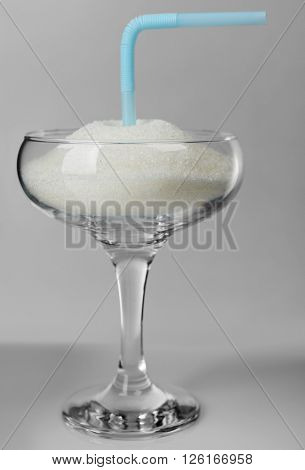 Margarita glass with granulated sugar and cocktail straw on grey background